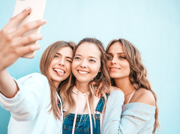 Three young smiling hipster women in summer clothes.girls taking selfie self portrait photos on smartphone.models posing in the street near wall.female showing positive face emotions. Free Photo