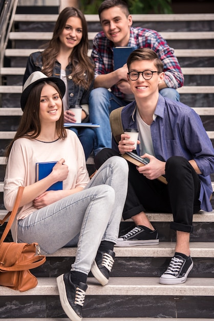 Three young students learning on stairs in college. Premium Photo