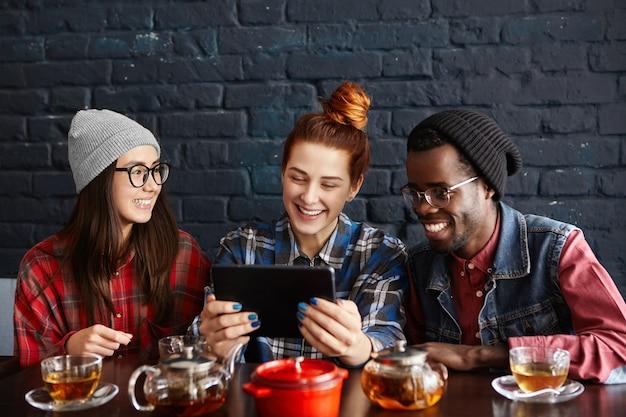 Трое молодых стильных людей разных рас смотрят онлайн-видео на обычном цифровом планшете, обедая вместе в ресторане Бесплатные Фотографии