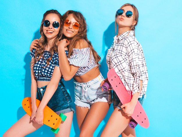 Three young stylish sexy smiling beautiful girls with colorful penny skateboards. women in summer checkered shirt clothes posing in sunglasses. positive models having fun Free Photo