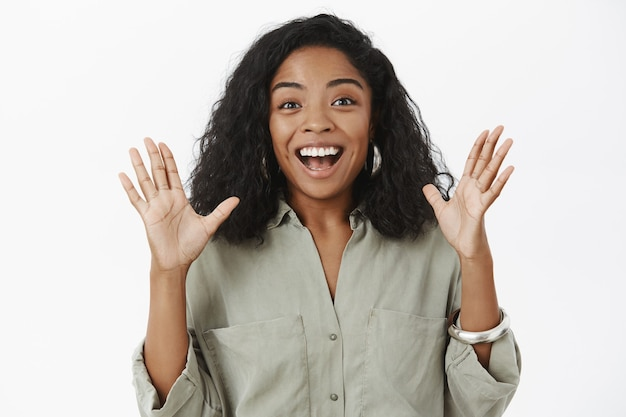 Thrilled talkative happy african american woman with curly hairstyle in trendy outfit raising palms gesturing joyfully and smiling delighted Free Photo