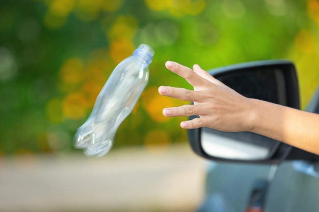 Throwing plastic bottle out from car window Free Photo