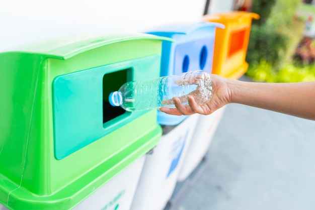 Throwing plastic water bottle into recycle bin Premium Photo