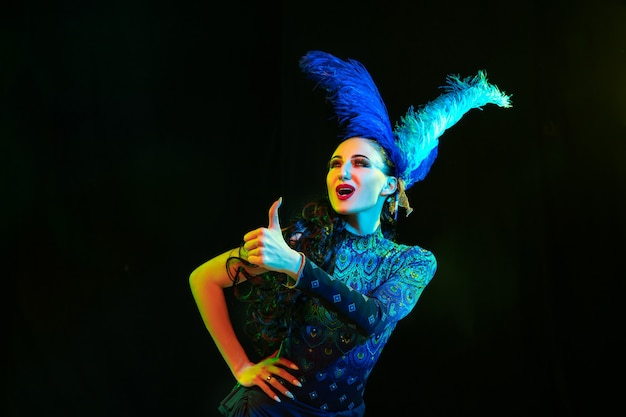 Thumb up. beautiful young woman in carnival, stylish masquerade costume with feathers on black wall in neon light. copyspace for ad. holidays celebration, dancing, fashion. festive time, party. Free Photo