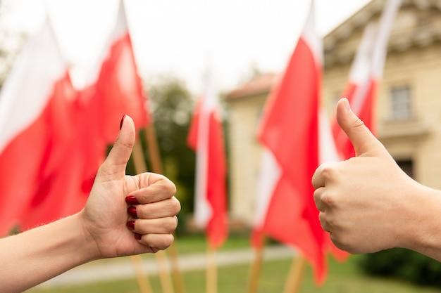 Жест пальца вверх с флагами польши позади Premium Фотографии