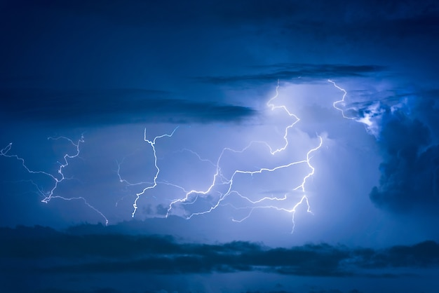 Thunder storm lightning strike on the dark cloudy sky background at night. Premium Photo