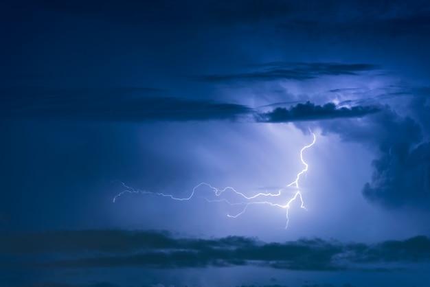 Thunder storm lightning strike on the dark cloudy sky background at night. Premium Photo