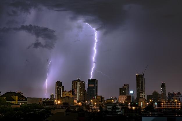 Thunderstorm lightning over city skyline at night in bangkok, asia Premium Photo