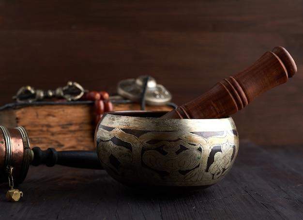 Тибетская поющая медная чаша с деревянной колотушкой на коричневом ву Premium Фотографии