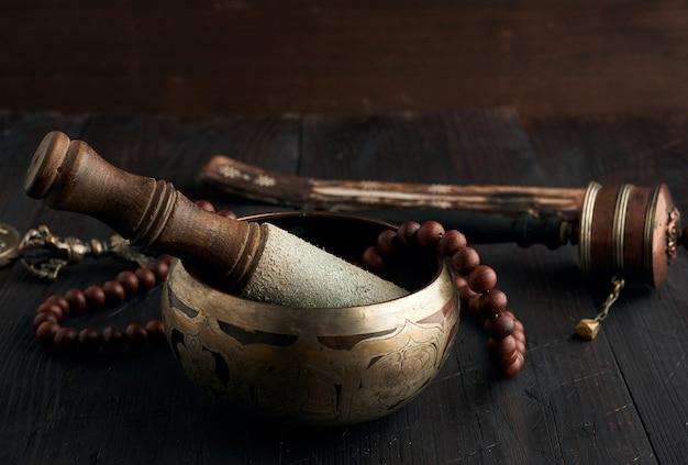 Медная поющая тибетская чаша с деревянной колотушкой на коричневом деревянном столе, предметы для медитации и нетрадиционной медицины Premium Фотографии