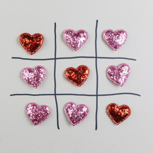 Tic-tac-toe with decorative sparkling hearts Free Photo