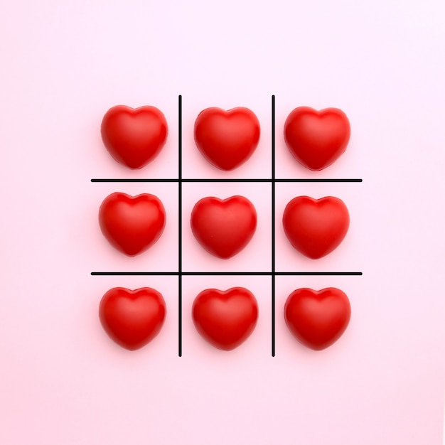 Tick tack toe made from red heart on pink background. valentine's day concept. minimal style. Premium Photo