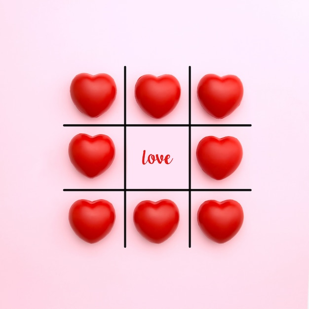 Tick tack toe made from red heart on pink background with love word in middle. valentine's day concept. minimal style. Premium Photo