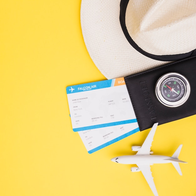 Tickets with passport, hat and plane Free Photo