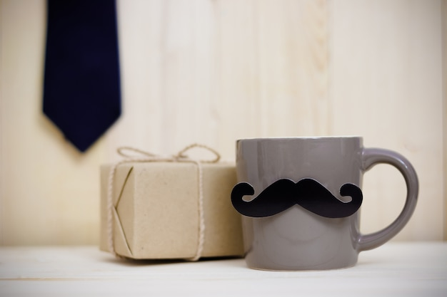 Tie, gift box, paper mustache, coffee cup on wooden background with copy space. happy father's day. Premium Photo