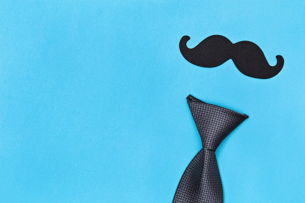 Tie and mustache on blue surface Premium Photo