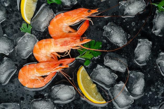 Тигровые креветки со льдом, лимоном и петрушкой на темном фоне. плоская планировка, копия пространства Premium Фотографии