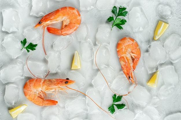 Тигровые креветки со льдом, лимоном и петрушкой. продовольственный фон. плоская планировка, вид сверху Premium Фотографии
