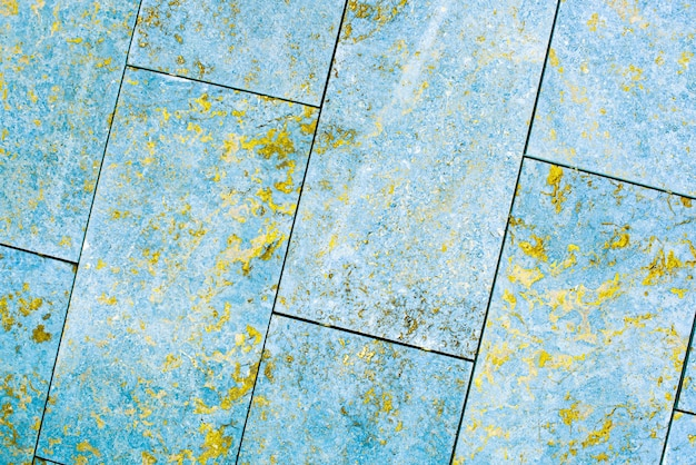 Tile, marble, concrete aged texture. old, vintage blue, fortuna gold background. gold with roughness and cracks. Premium Photo