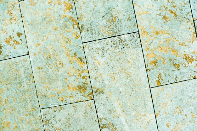 Tile, marble, concrete aged texture. old, vintage celadon green, fortuna gold background. gold with roughness and cracks. Premium Photo
