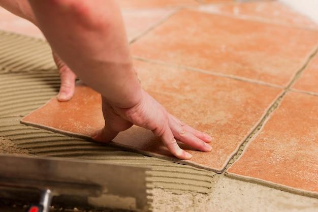 Tiler tiling tiles on the floor Premium Photo