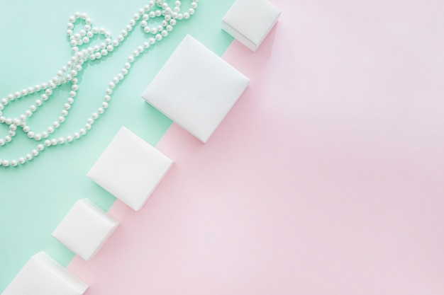 Tilt row of different white boxes with pearls necklace on pastel background Free Photo