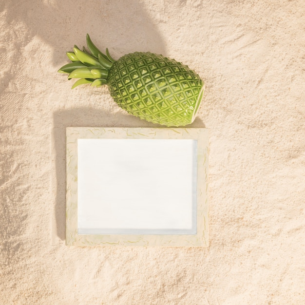 Timber picture frame and pineapple on sand Free Photo