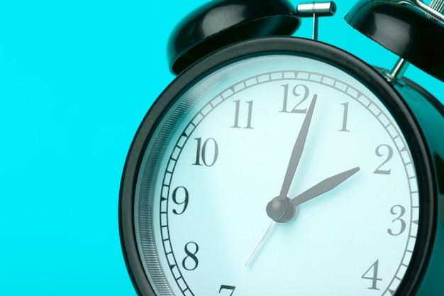 Time background concept. vintage classic alarm clock on blue empty background. time management comcept Premium Photo