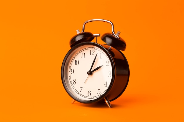 Time background concept. vintage classic alarm clock on orange empty background. time management comcept Premium Photo