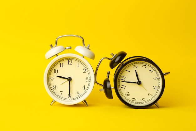 Time background concept. vintage classic alarm clock on yellow empty background. time management comcept Premium Photo