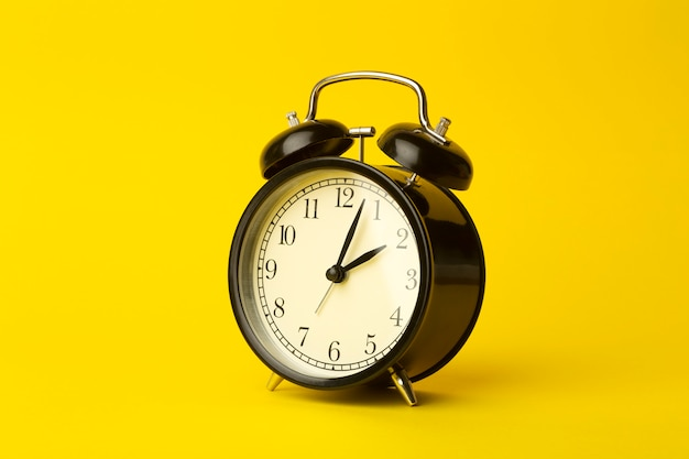 Time background concept. vintage classic alarm clock on yellow empty background. time management comcept Premium Photo