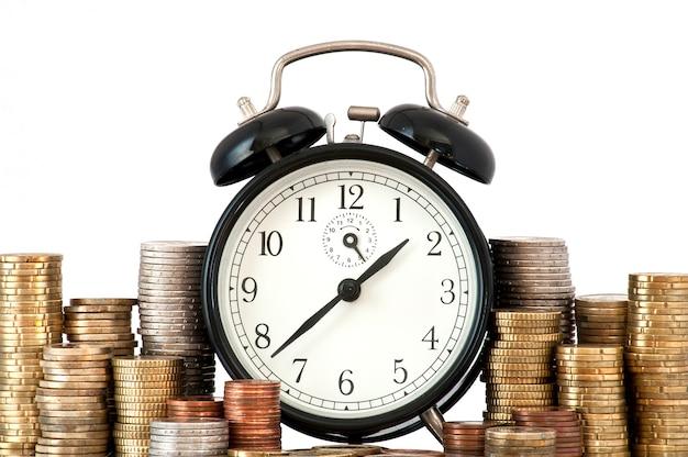 Концепция time is money: будильник и много монет евро Бесплатные Фотографии