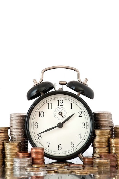 Time is money concept: alarm clock and lots of euro coins Free Photo