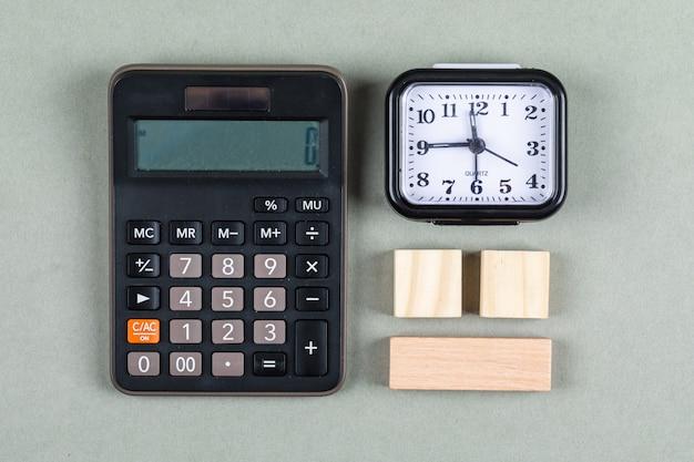 拡大鏡、木製のブロック、電卓、灰色の背景の上面に時計の時間管理と会計の概念。横長画像 無料写真