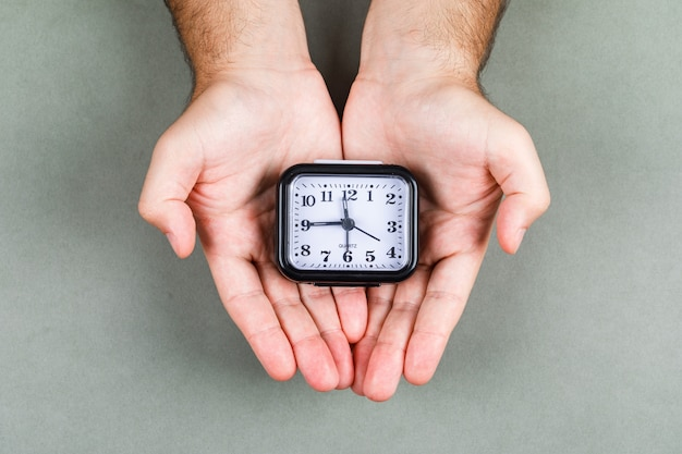 時間管理と灰色の背景の上面に時計のコンセプトを刻む時計。時計を保持している手。横長画像 無料写真