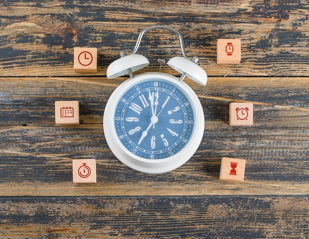 Time management concept with wooden blocks with icons, big clock on wooden table flat lay. Free Photo