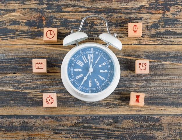 Concetto di gestione del tempo con blocchi di legno con icone, grande orologio sul tavolo di legno piatto laici. Foto Gratuite
