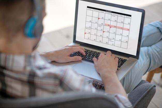 時間の管理。彼のオンライン作業カレンダーをチェックしている青年実業家 Premium写真