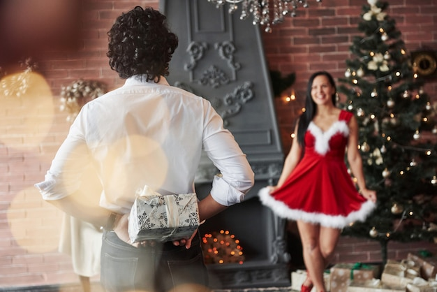 Time for sharing love and presents. man stands and holds gift box behind. woman in red dress will now receive christmas gift from boyfriend Premium Photo