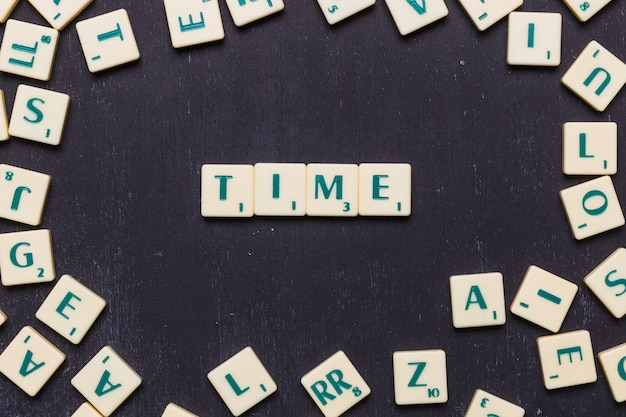 Time text on scrabble letters on black backdrop Free Photo