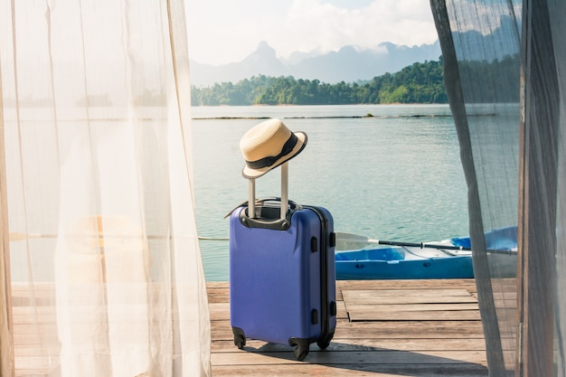 Time to Relax, suitcase standing on the floor with cap out the room, travel lifestyle. Premium Photo