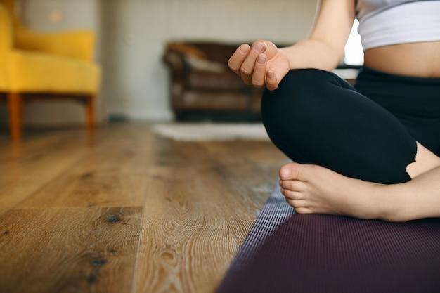 減速する時間。足を組んでマットの上に座って、ヨガ中に瞑想を練習している認識できない若い裸足の女性のトリミングされた画像。 無料写真