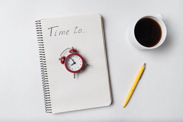 Записная книжка с надписью time to. блокнот и старинный будильник. планирование и кофе. Premium Фотографии