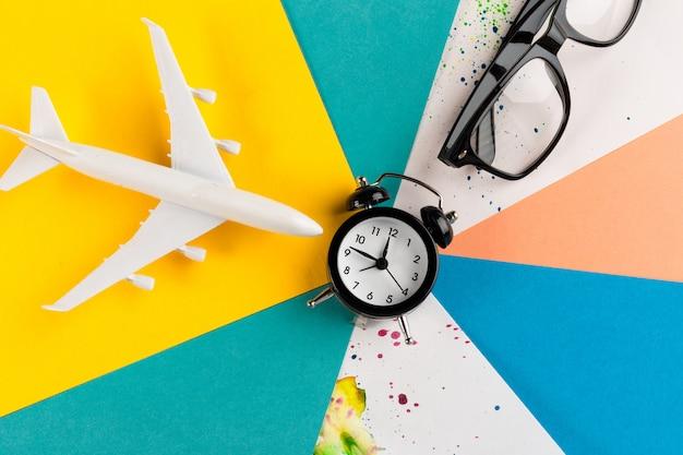 Time to travel concept. plastic plane jet toy passenger with alarm clock Premium Photo