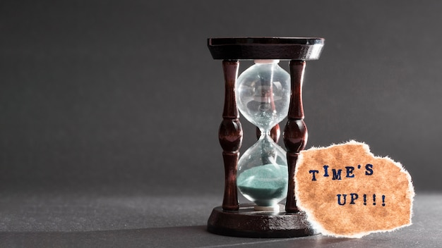 Times up text on torn paper near the hour glass against gray background Premium Photo