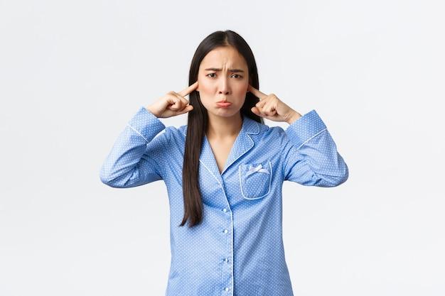 Робкая и грустная азиатская девушка в синей пижаме надувается и скулит Premium Фотографии