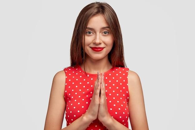 Робкая брюнетка молодая женщина позирует у белой стены Бесплатные Фотографии