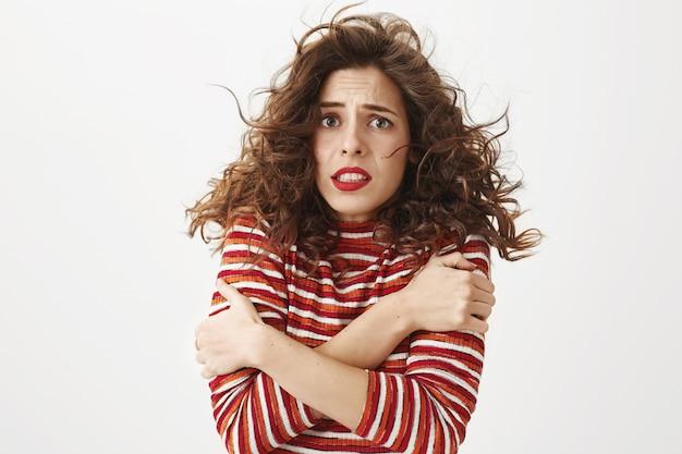 ウォームアップをしようと震え、風の強い天気で冷たく感じる臆病な女性 無料写真