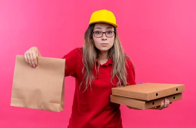 カメラを見てピザの箱と紙のパッケージを保持している赤いポロシャツと黄色の帽子の臆病な若い配達の女の子 無料写真