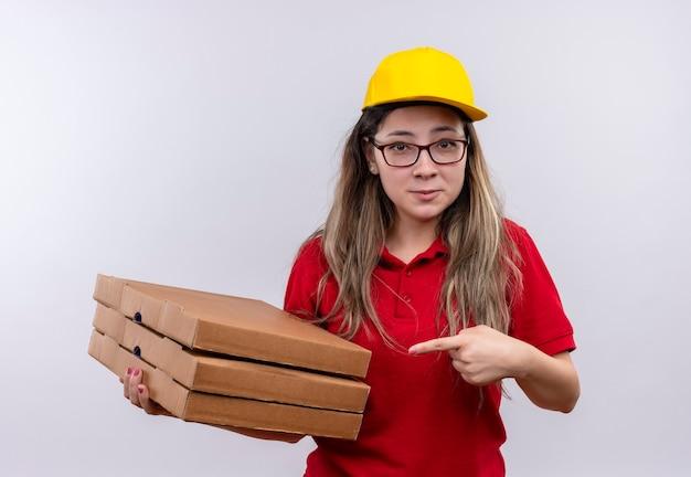 赤いポロシャツと黄色い帽子の臆病な若い配達の女の子は、笑顔でそれに指で指しているピザの箱のスタックを保持しています 無料写真